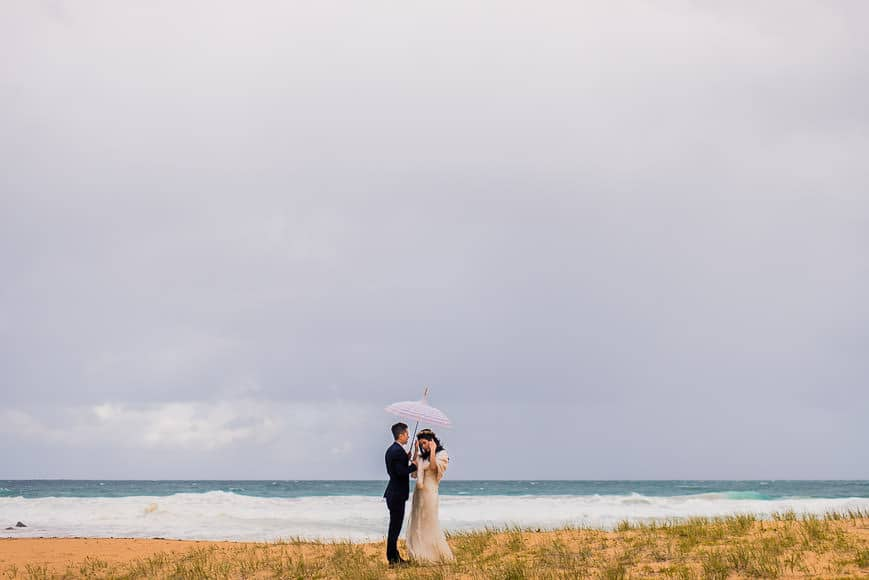 Bride and Groom with umbrella on Whale Beach