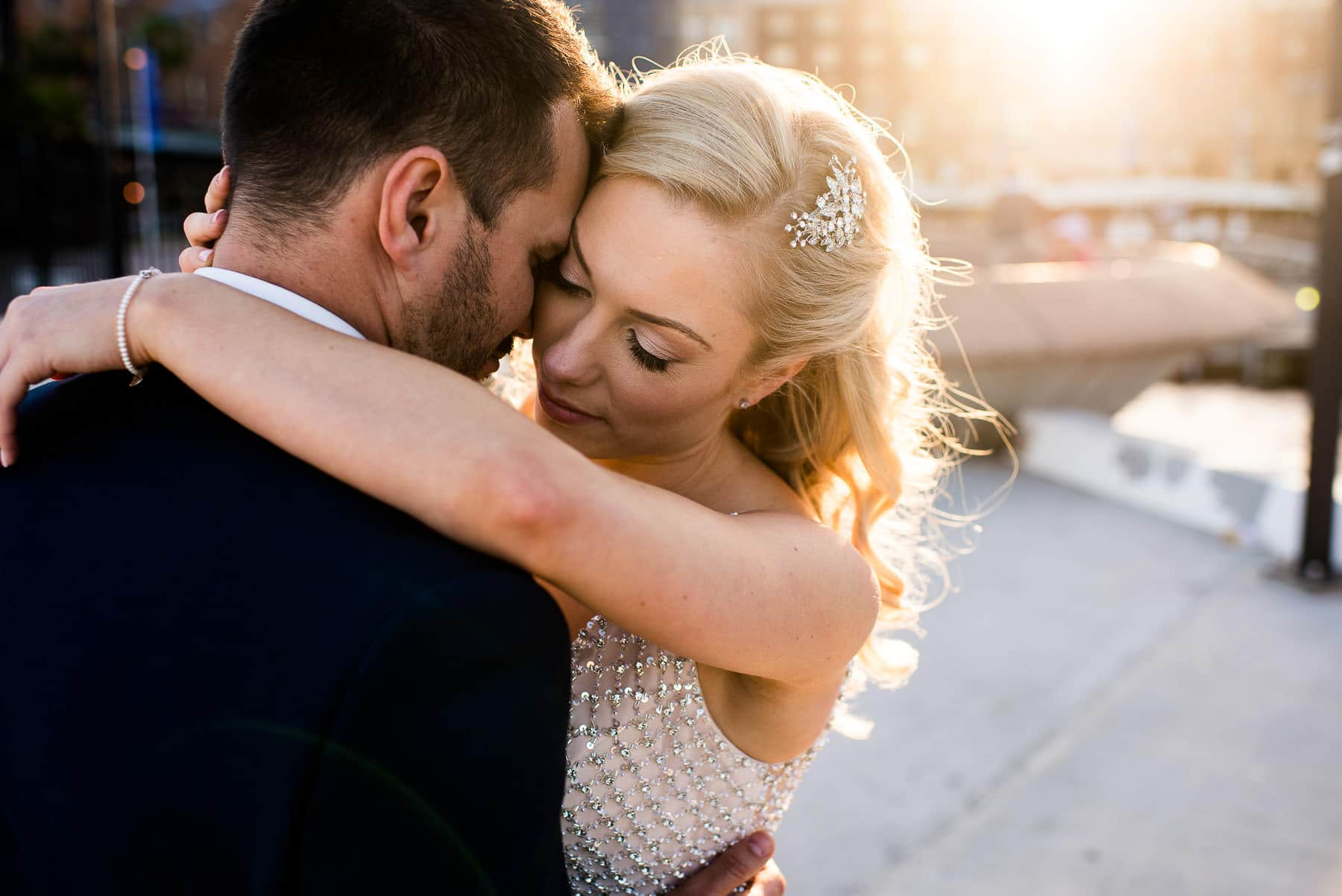 candid wedding photography of bride hugging groom with sun flare