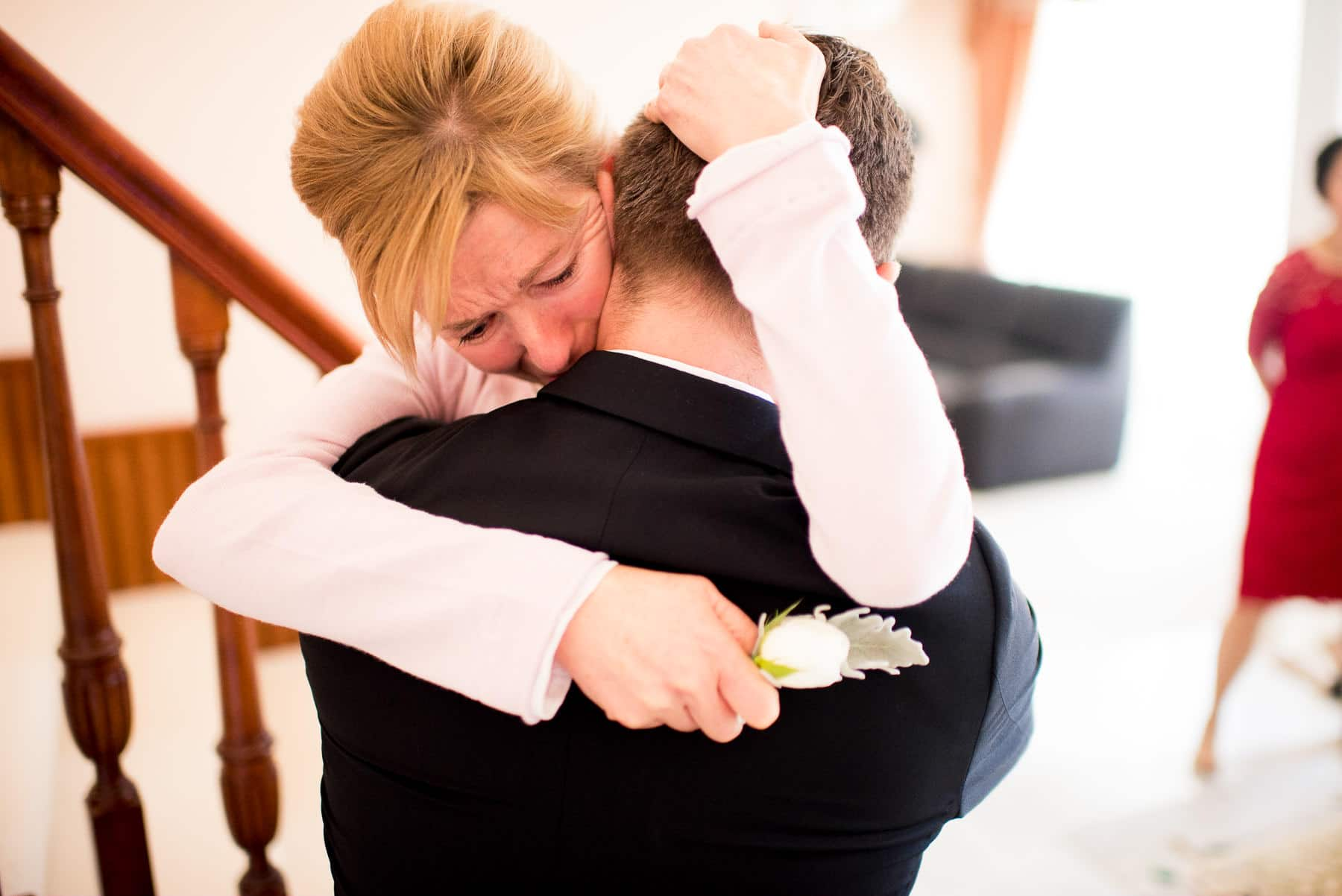 groom's mother hugs groom on wedding day