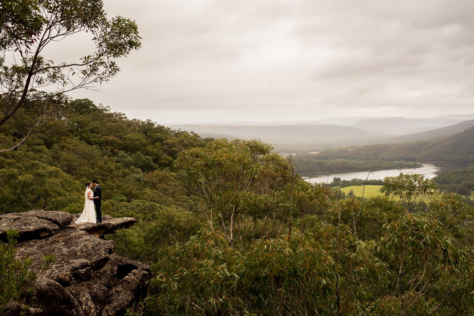 Kangaroo Valley Wedding | Newly weds embrace on cliff edge overlooking forest