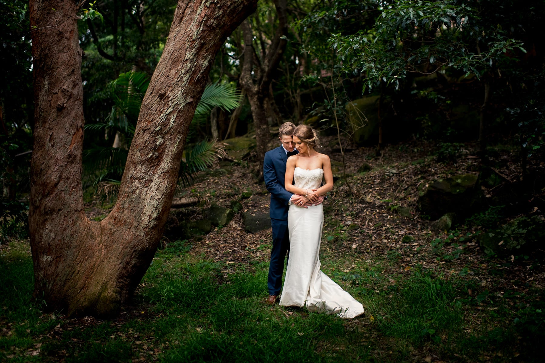 Bride and groom hold each other under tree in Parsley Bay after wedding ceremony