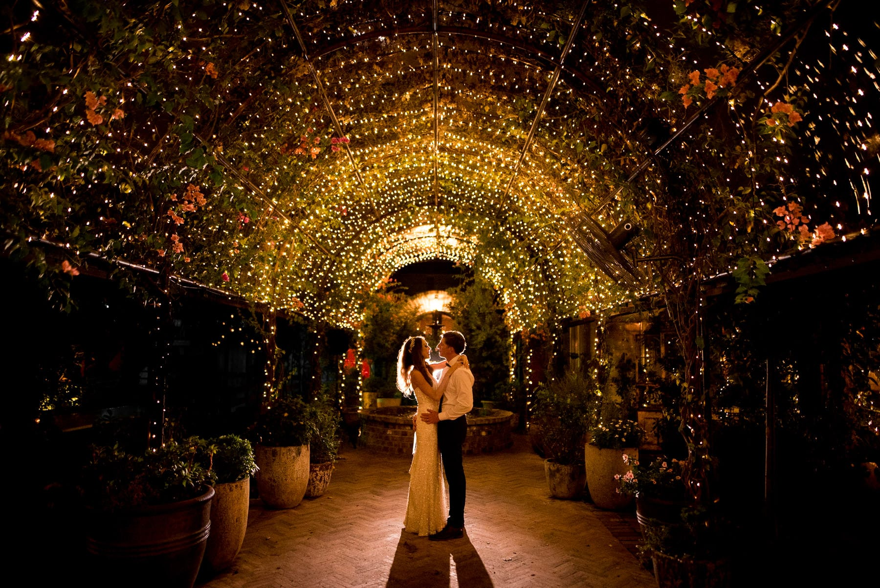 beautiful photo of newly weds under fairy lights at their wedding