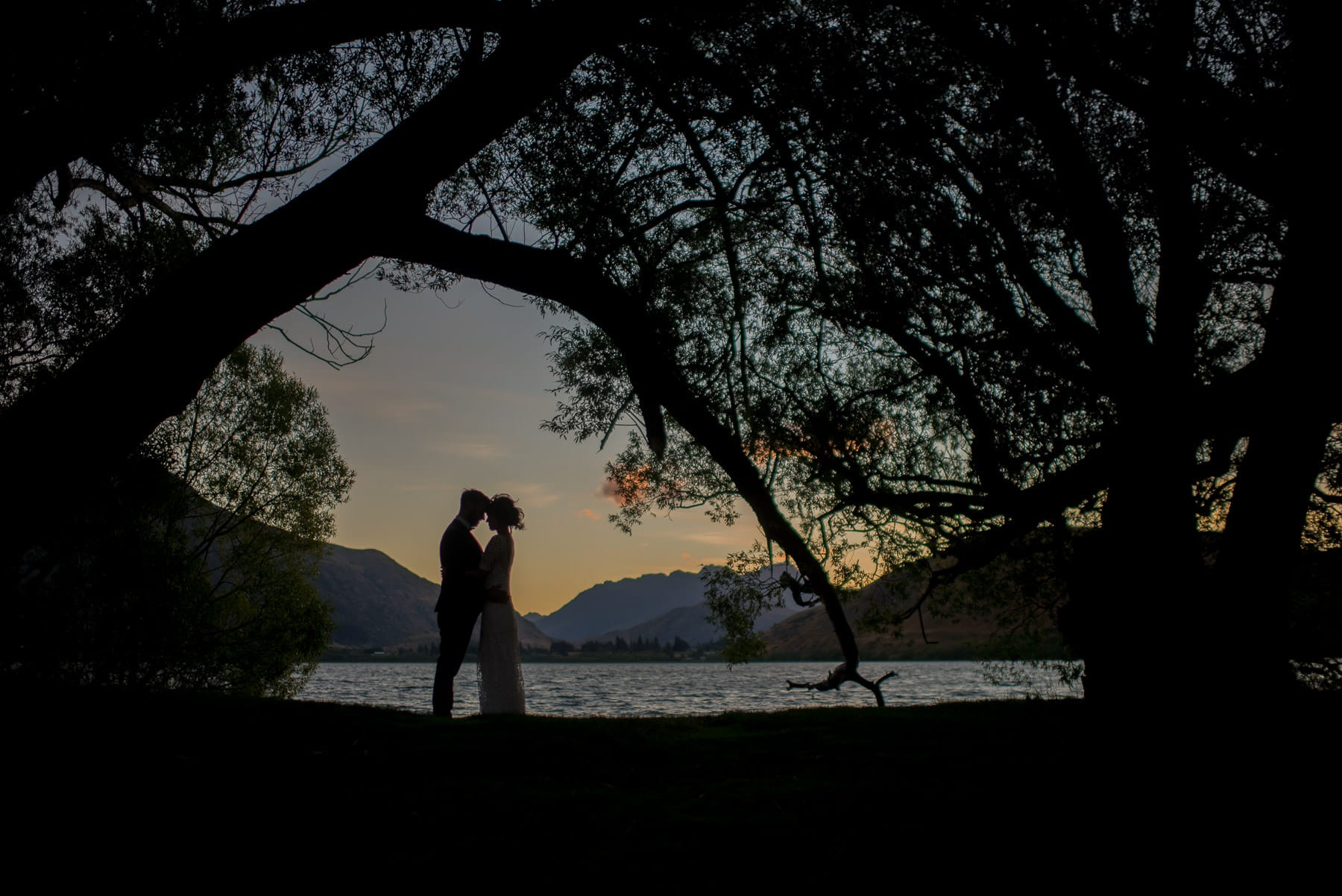 sunset at Lake Hayes in Uqeenstown silhouette of bride and groom