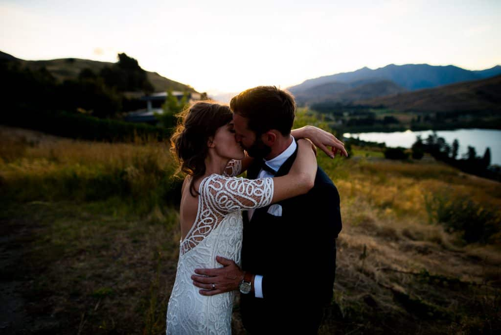 bride and groom kissing after sunset in Queenstown