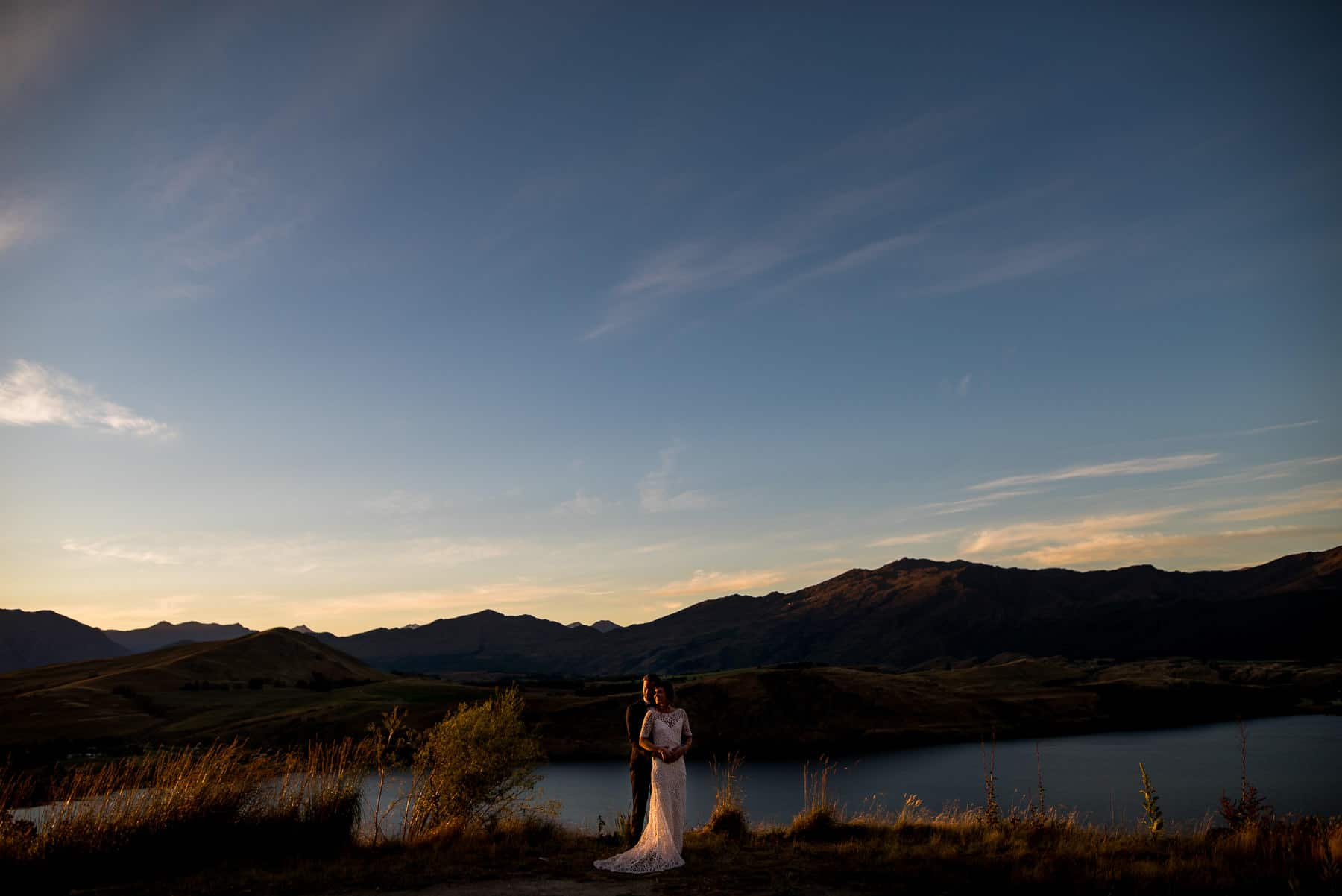 beautiful image of queenstown lakes and mountains with newly weds at New Zealand destination wedding