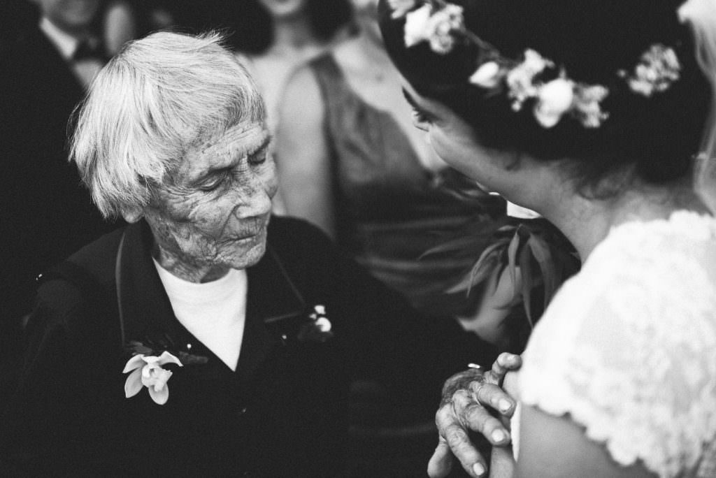 Black and White Wedding Photography | Grandma touches bride tenderly at wedding ceremony
