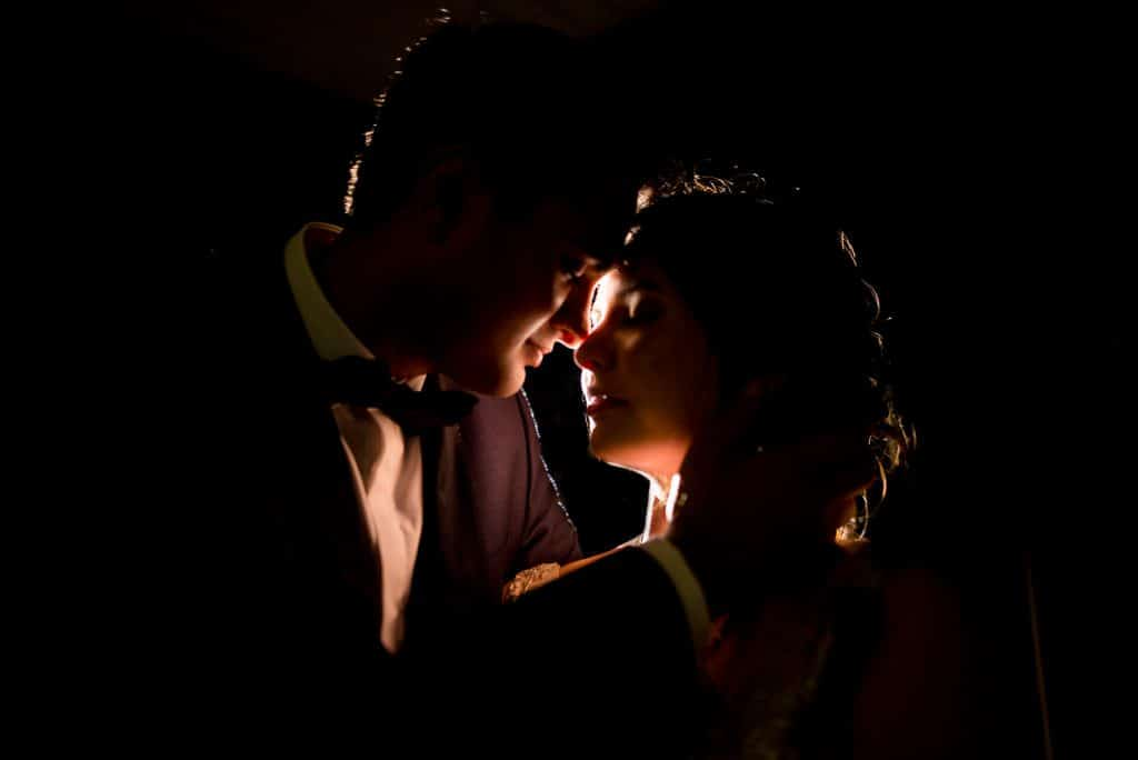 Backlit photo of Indian wedding | bride and groom kissing at night
