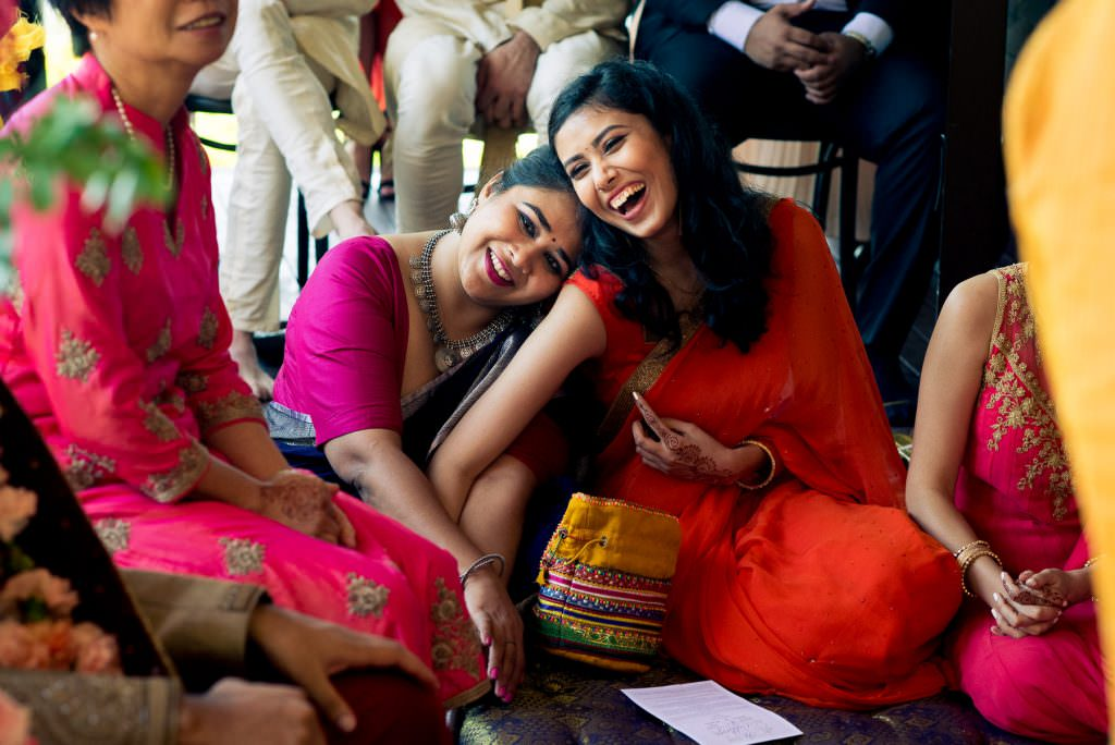 Indian bridesmaids laughing at wedding ceremony