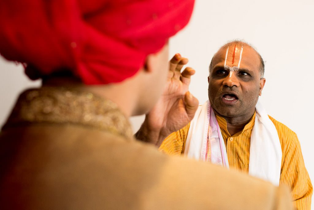 Indian Priest blesses groom during Indian wedding photography