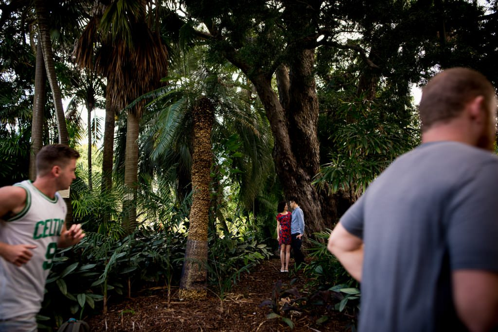 joggers run past couple hugging in trees in botanic gardens