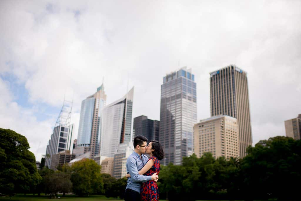 couple kissing in front of Sydney city skyline during engagement session with Gold Hat Photography