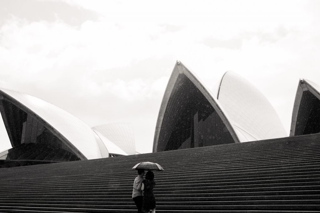 couple under umbrella in front of Sydney Opera House