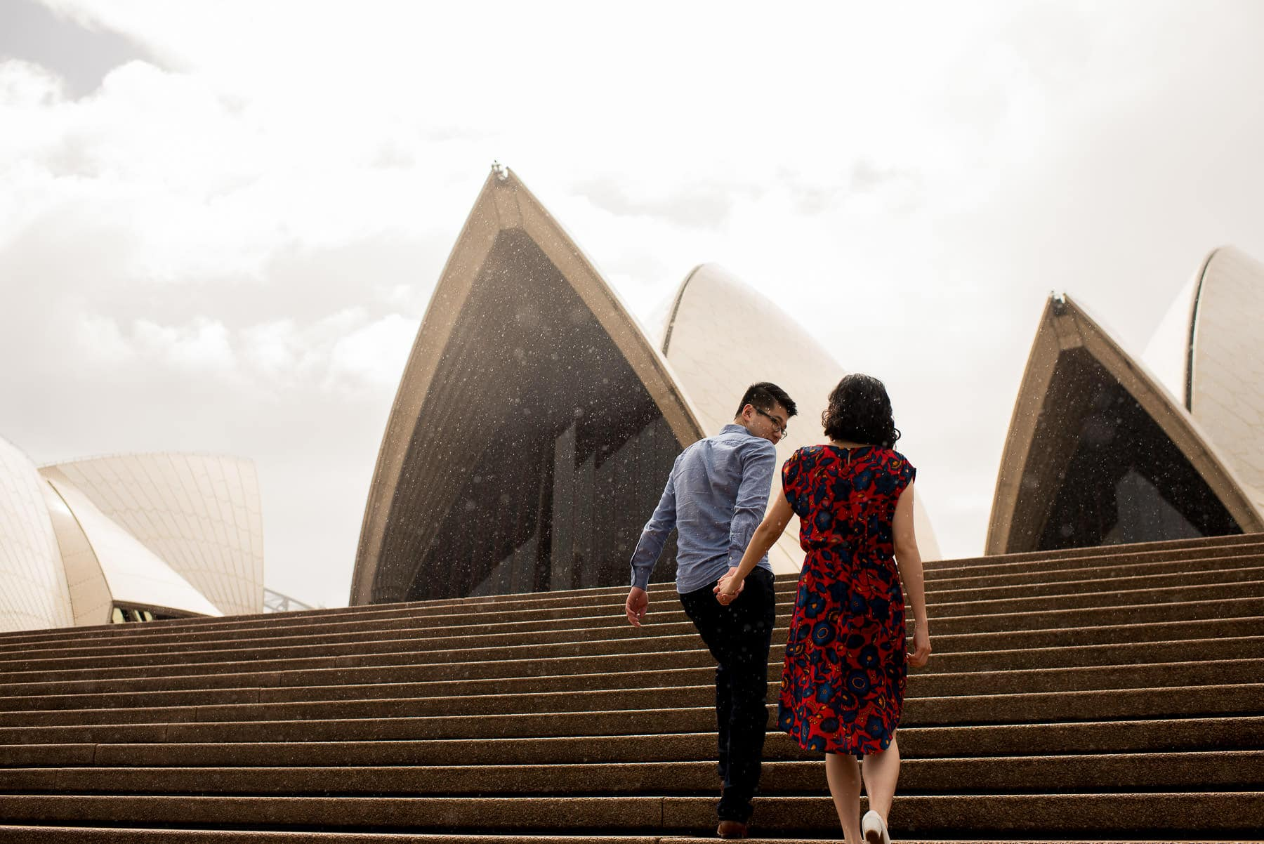 guy leads girl up steps at Opera House during engagement photography session on a rainy day