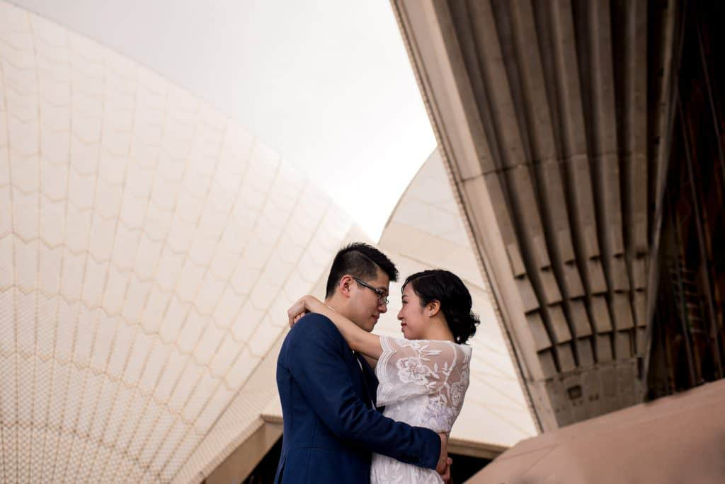 Opera house engagement photography - couple hugging in front of sails
