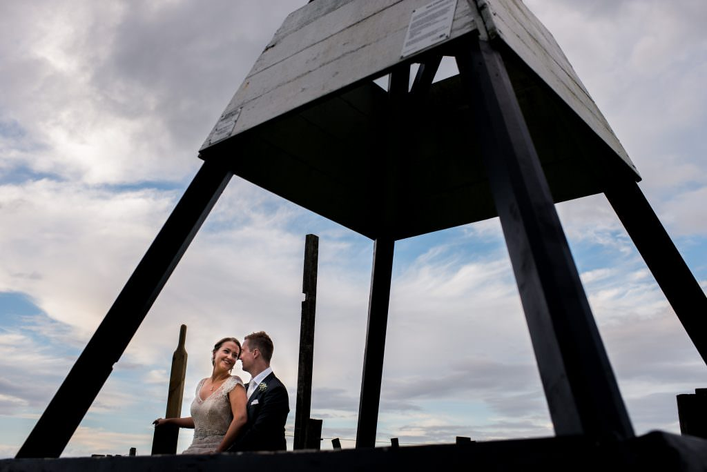 Bride and groom hug under trig point marker